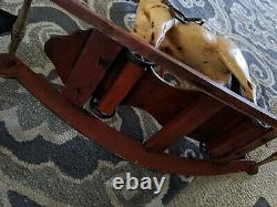 VINTAGE HANDCRAFTED WOODEN ROCKING HORSE with cast iron wheels & leather saddle